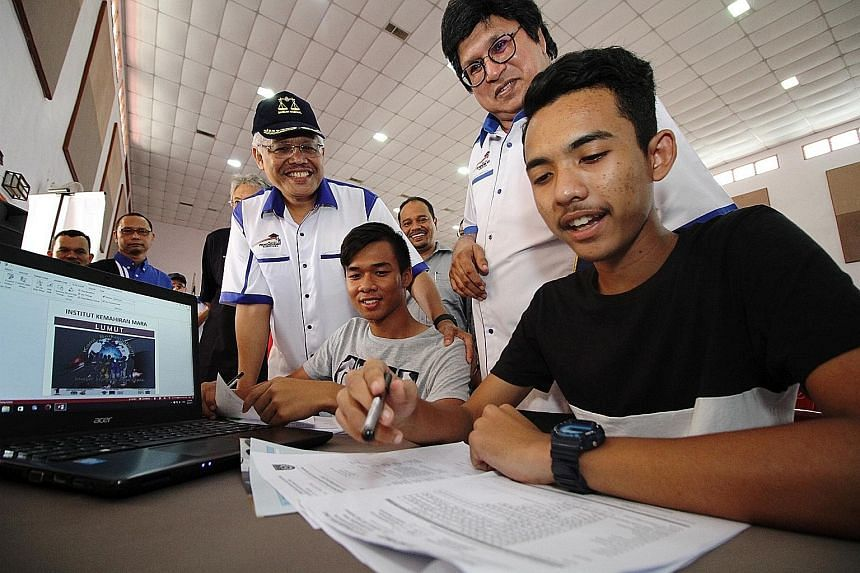 Domestic Trade, Cooperatives and Consumerism Minister Hamzah Zainudin (in cap) and Bumiputera Education Tour main committee chairman Sahol Hamid Abu Bakar observing as students in Perak apply for college. Under Malaysia's affirmative action New Econo