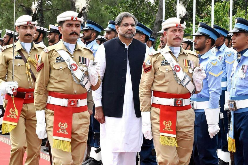 Pakistan's Prime Minister Shahid Khaqan Abbasi (centre) reviews the honour guard during a welcome ceremony at the Prime Minister House in Islamabad on Aug 3, 2017.