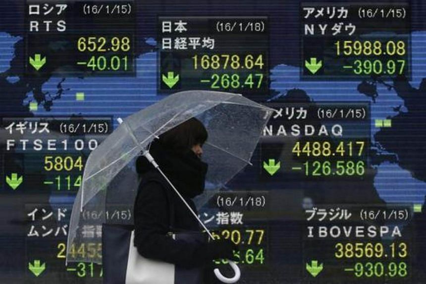 A pedestrian holding an umbrella walks past at an electronic board showing the stock market indices of various countries outside a brokerage in Tokyo, Japan, on Jan 18, 2016.