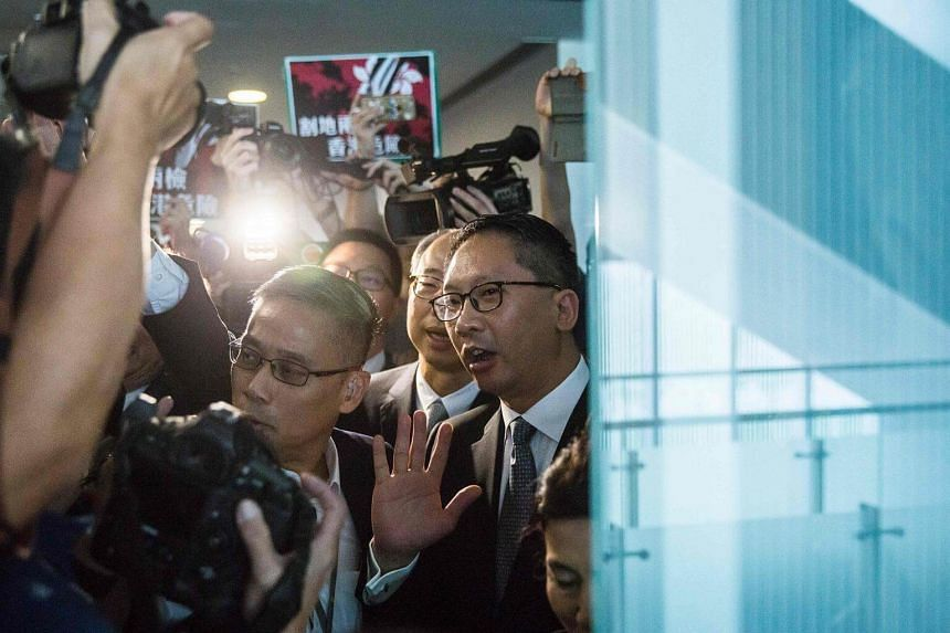 Hong Kong's secretary for justice Rimsky Yuen (centre) gestures to the media after a meeting to discuss the high-speed rail link at the Legislative Council building in HongKong on Aug 3, 2017.