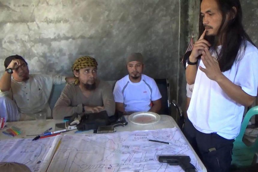 This screengrab taken from handout video released by the Philippine Army on June 18, 2017, shows Abdullah Maute (right) looking at an improvised map of Marawi, while Isnilon Hapilon (second, left), leader of hardline group Abu Sayyaf looks on, as the