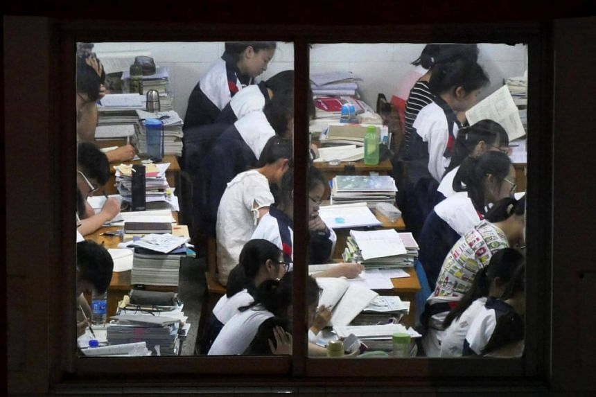 Students study in their classrooms at night at a school in Yangzhou in China's eastern Jiangsu province, on May 31, 2017.