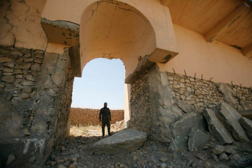 A member of Iraqi security forces inspects the remains of wall panels and colossal statues of winged bulls, destroyed by Islamic State militants are seen in the Assyrian city of Nimrud.