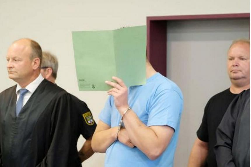 The defendant Sebastian F covers his face with a folder during a verdict reading in a courtroom of the regional court in Dessau Rosslau, Germany, on August 4 2017.