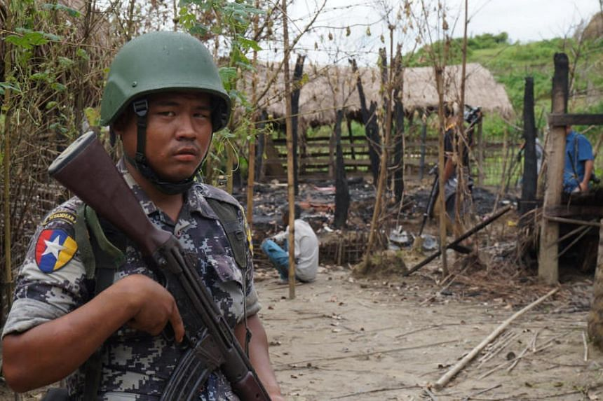A Myanmar border guard police officer stands guard in front of the remains of a house burned down in a clash between suspected militants and security forces in Tin May village, Buthidaung township, northern Rakhine state, Myanmar on July 14, 2017.