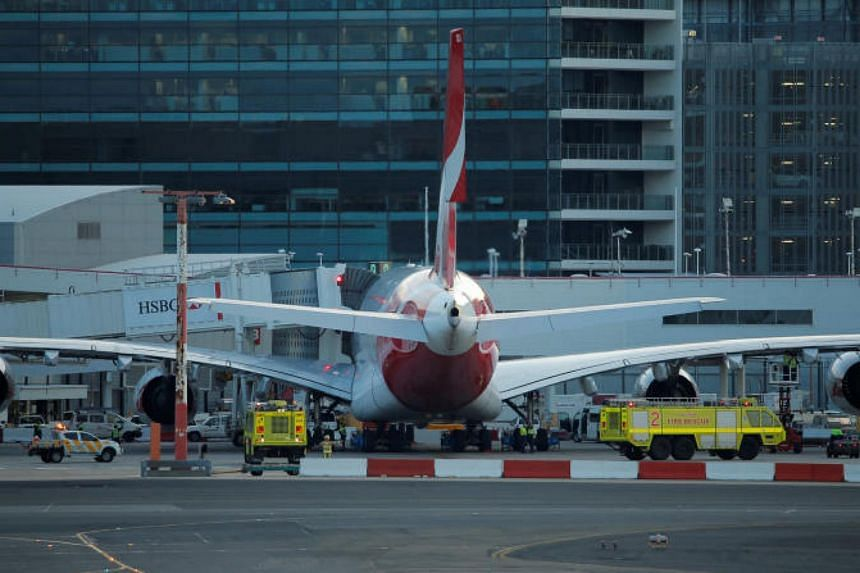 Fire engines position alongside a Qantas A380 aircraft after the Dallas-bound flight QF7 was forced to return and make an emergency landing due to mechanical fault at Sydney International Airport in Australia on Aug 4, 2017.