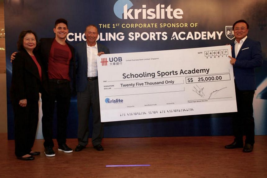 The Schoolings accepting a corporate sponsor donation of $25,000 from Group Managing Director of Krislite Jimmy Teo to the the Joseph Schooling Academy.
