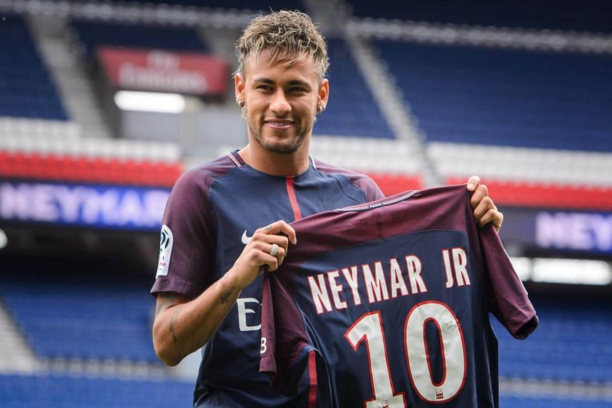Brazilian striker Neymar Jr. poses for photographs with his new PSG jersey after a press conference at the Parc des Princes stadium in Paris, on Aug 4, 2017.