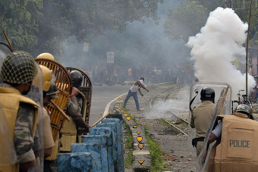 """A supporter of a separate """"Gorkhaland"""" within West Bengal hurling objects at the police during a strike at Sukna village in the Darjeeling district, near Siliguri, on July 29. Tourism has also been badly hit by the dispute in which the main Gorkha gr"""
