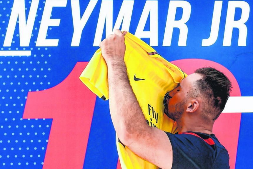 A Paris Saint-Germain fan kissing a replica of Neymar's new jersey yesterday, after purchasing it at the club store on Champs Elysees. Neymar insisted that he chose to leave Barcelona for PSG against the advice of his father.
