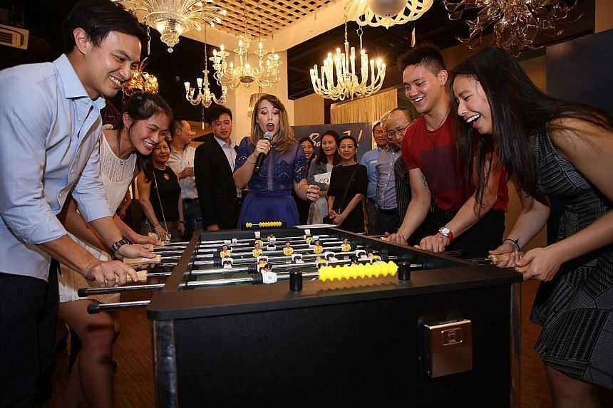 A team led by Teo Zhen Ren (left) takes on another led by Joseph Schooling (second right) at table football to raise funds for the Schooling Sports Academy.