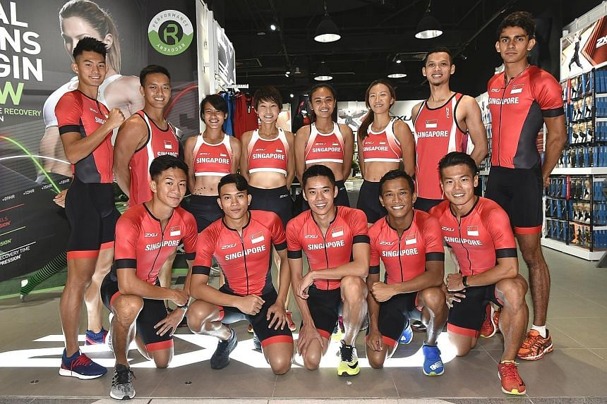 National athletics team members posing in their new sponsored competition attire, 2XU, at Suntec City yesterday.