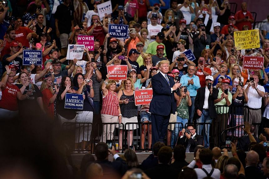 Mr Donald Trump on stage after speaking at a rally on Thursday in Huntington, West Virginia - the heartland of his support. The President lashed out at the Democrats before a crowd of nearly 10,000.