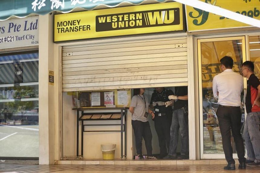 Police conducting investigations at a Western Union branch, where an armed robbery took place, in Ubi on Tuesday morning.