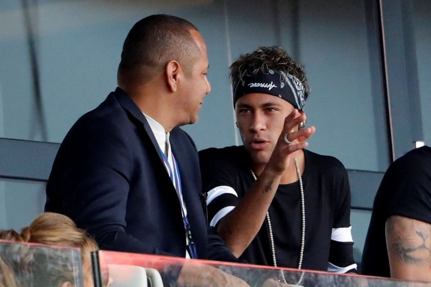 PSG's Neymar talks with his father, Neymar Snr (left), while in the stands watching his new team play.