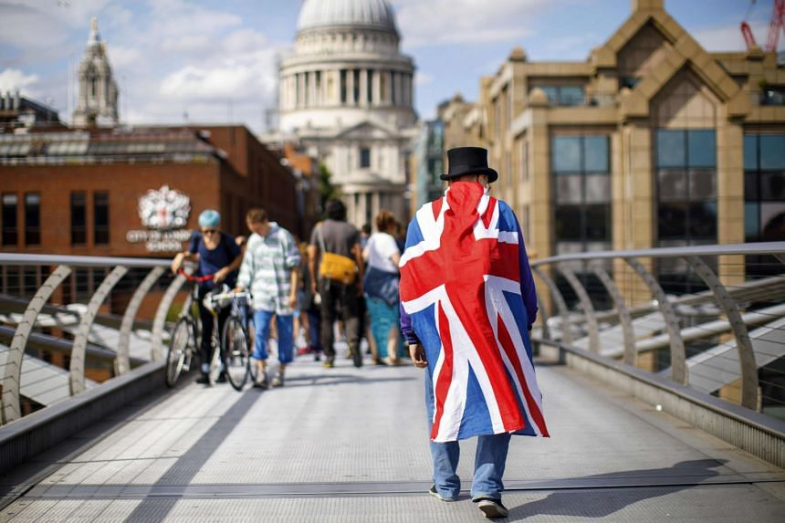 A man wears a top hat and a Union Flag as he crosses the Millennium Bridge in London.