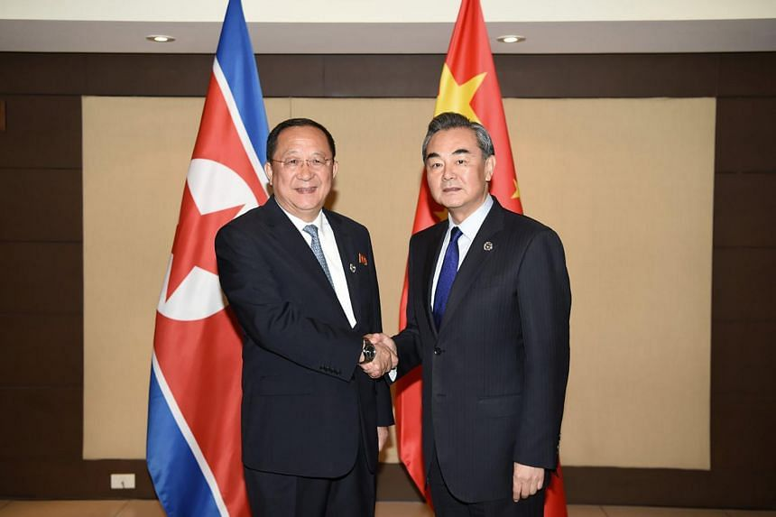 China's Foreign Minister Wang Yi (right) shakes hands with North Korea's Foreign Minister Ri Yong Ho (left) during their bilateral meeting on the sidelines of the Association of Southeast Asian Nations (ASEAN) regional security forum in Manila on Aug