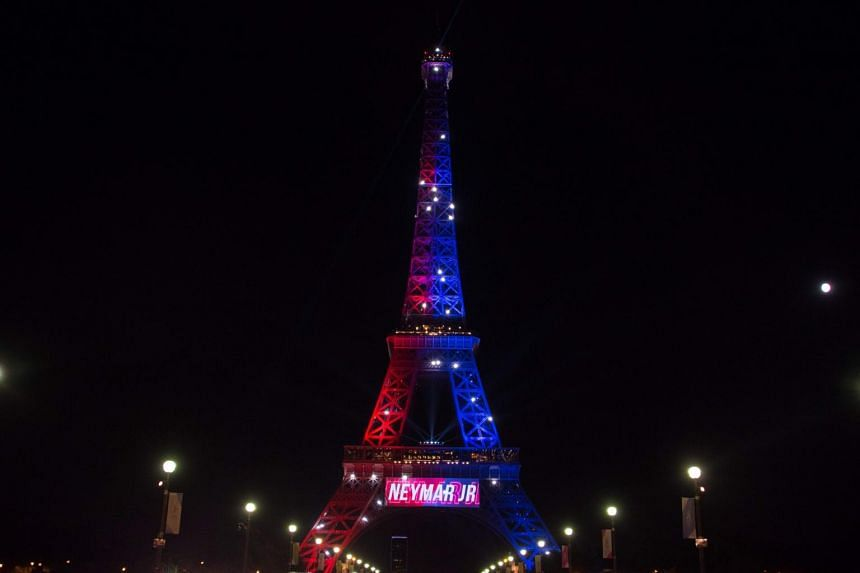 """Red and blue lights and a welcoming message that reads in French """"Neymar Jr."""" adorn the Eiffel Tower to celebrate the arrival of Brazilian footballer Neymar to Paris on Aug 5, 2017 after his signing with the Paris Saint-Germain (PSG) football club."""