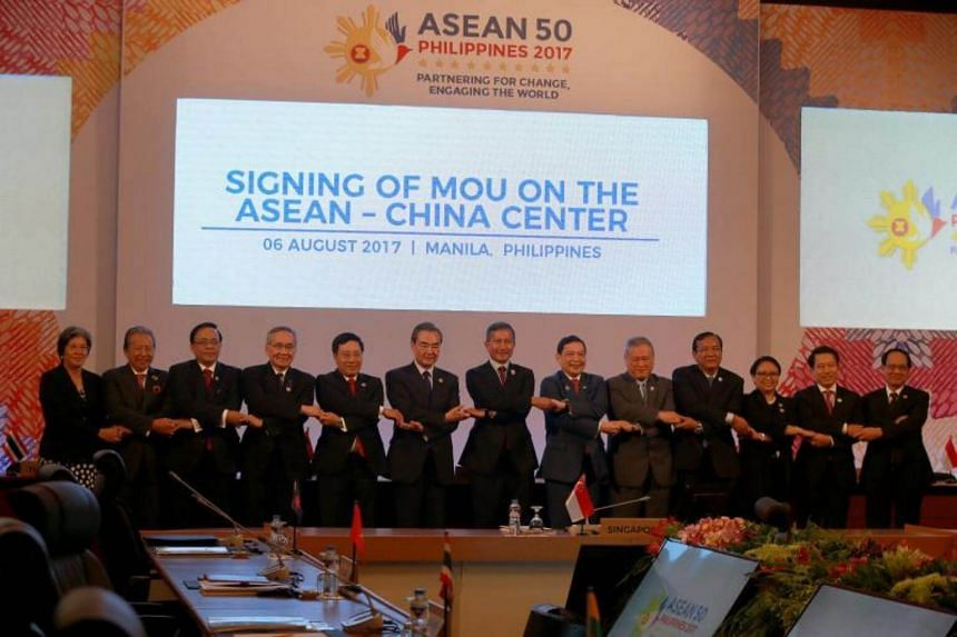 Chinese Foreign Minister Wang Yi (sixth from left) and Asean foreign ministers linking arms during a meeting in Manila on Aug 6, 2017.