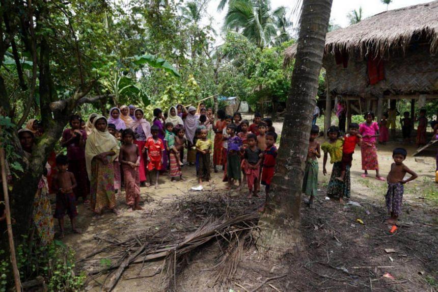 Rohingya villagers watch as international media visit Maung Hna Ma village, Buthidaung township, northern Rakhine state, Myanmar on July 14, 2017.
