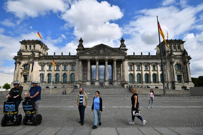 Two Chinese tourists were detained for making the banned Hitler salute in front of the German Reichstag building.