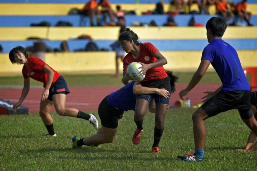 Ms Shuhadah getting tackled by one of the boys from the rugby team of Catholic Junior College during a friendly match with the National Women's Rugby Sevens Team at the Yio Chu Kang stadium.