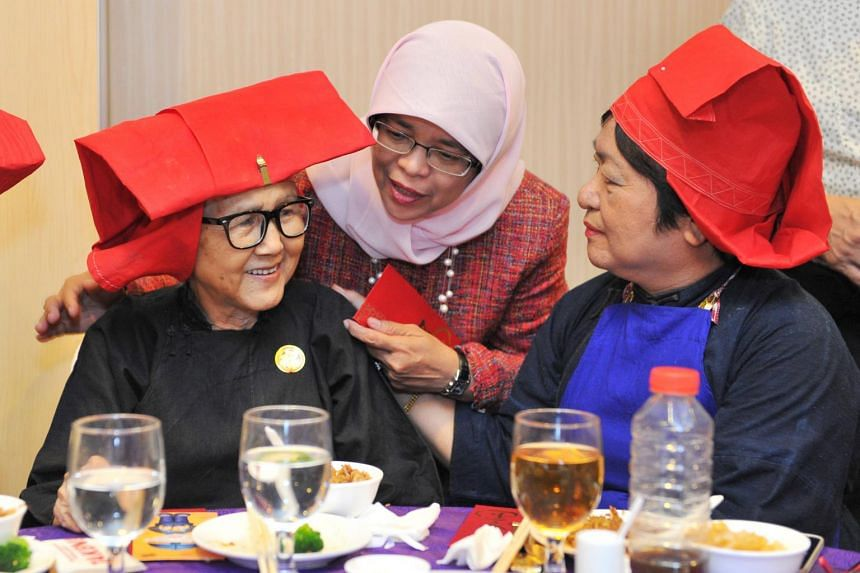 Madam Halimah Yacob interacting with former samsui woman Woo Yum Sum (left) and retiree Margaret Low, both from Redhill Moral Senior Activity Centre, at the Singapore Women's Association's Chinese New Year lunch on March 19, 2015.