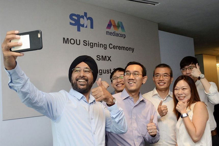 Executives from Singapore Press Holdings and Mediacorp pose for a wefie at the MOU signing for a new joint venture, dubbed Singapore Media Exchange.