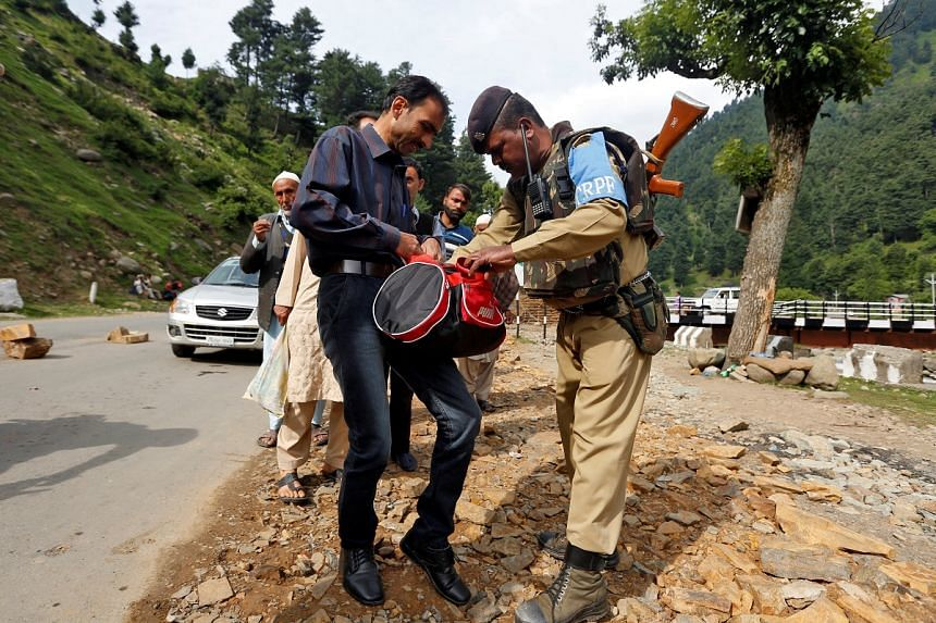 An Indian security force personnel checks the bag of a man near a base camp to the cave of Amarnath after seven Hindu pilgrims were killed on July 10.