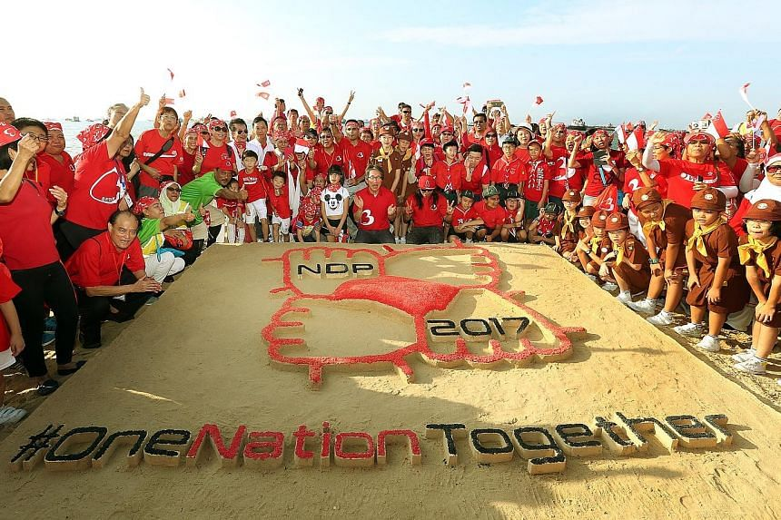 Together with over 800 Bedok residents and students, Mr Lim Swee Say unveiled the sand art sculpture, which depicts this year's National Day Parade logo, at East Coast Park yesterday morning.