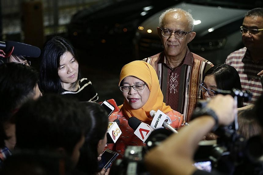 Madam Halimah Yacob, accompanied by her husband Mohammed Abdullah Alhabshee, speaking to the media after announcing her decision to run for president at the Marsiling National Day dinner yesterday.