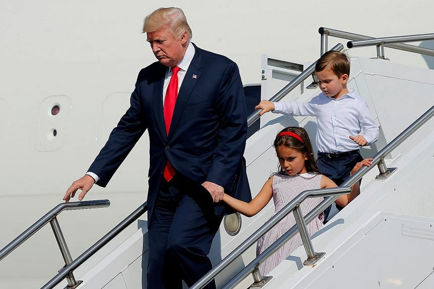 """President Donald Trump, with his grandchildren Arabella Kushner and Joseph Kushner, exiting Air Force One at Morristown Airport in Morristown, New Jersey, on Friday, for a summer """"working vacation"""" at his Bedminster estate."""