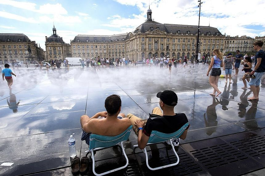 People refreshing themselves in the Water Mirror fountain in Bordeaux, France, last Friday. There has yet to be any sign of visitors to southern Europe being deterred by the heatwave.