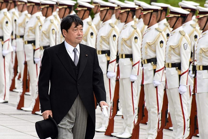 Japan's new Defence Minister Itsunori Onodera reviewing a guard of honour during a ceremony at the Defence Ministry in Tokyo on Friday. He has, since his first term as defence chief from December 2012 to September 2014, already been a vocal champion