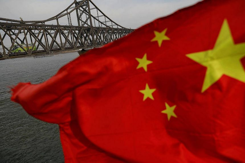 A Chinese flag is seen in front of the Friendship bridge over the Yalu River connecting Sinuiju, North Korea, and Dandong, China.