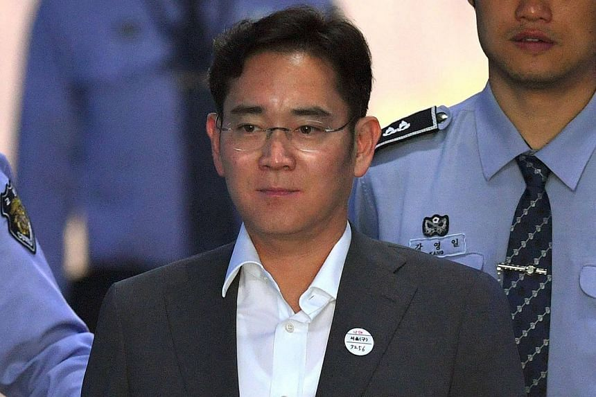Samsung's heir apparent Lee Jae Yong is escorted by prison guards as he arrives at the Seoul Central District Court on May 11, 2017.