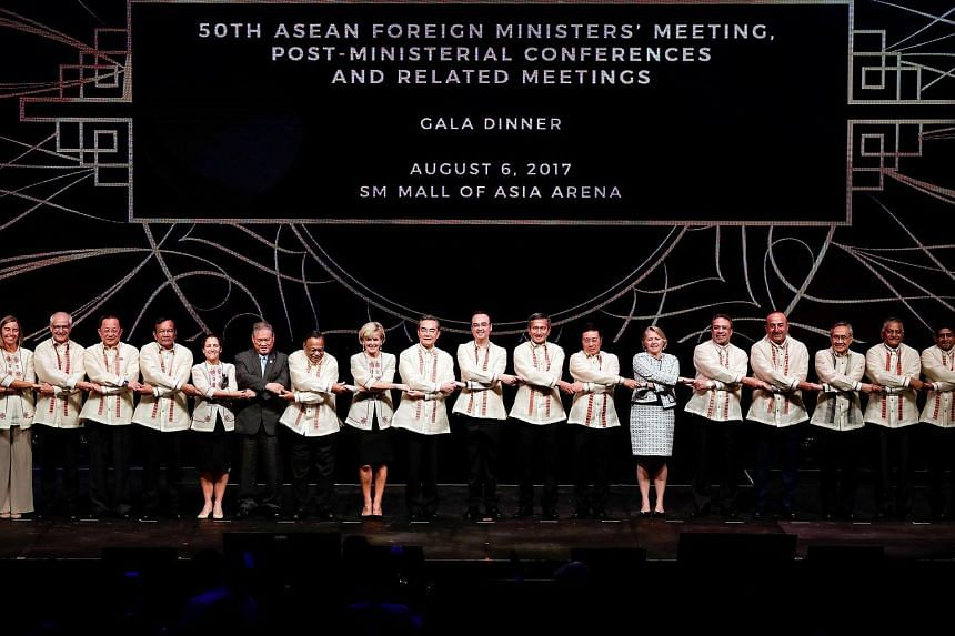 China's Foreign Minister Wang Yi, Philippine Foreign Secretary Alan Peter Cayetano and Singaporean Foreign Minister Vivian Balakrishnan link arms with ASEAN foreign ministers and their representatives during the Gala Dinner of the Association of Sout