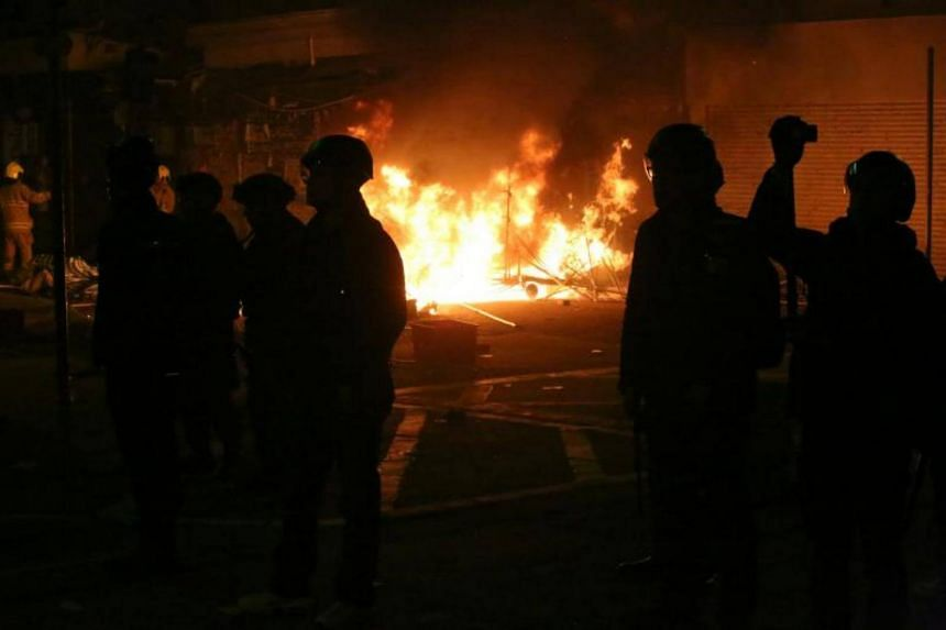 Hong Kong riot police silhouetted as rioters burn debris in the street, in Mongkok on Feb 9, 2016.