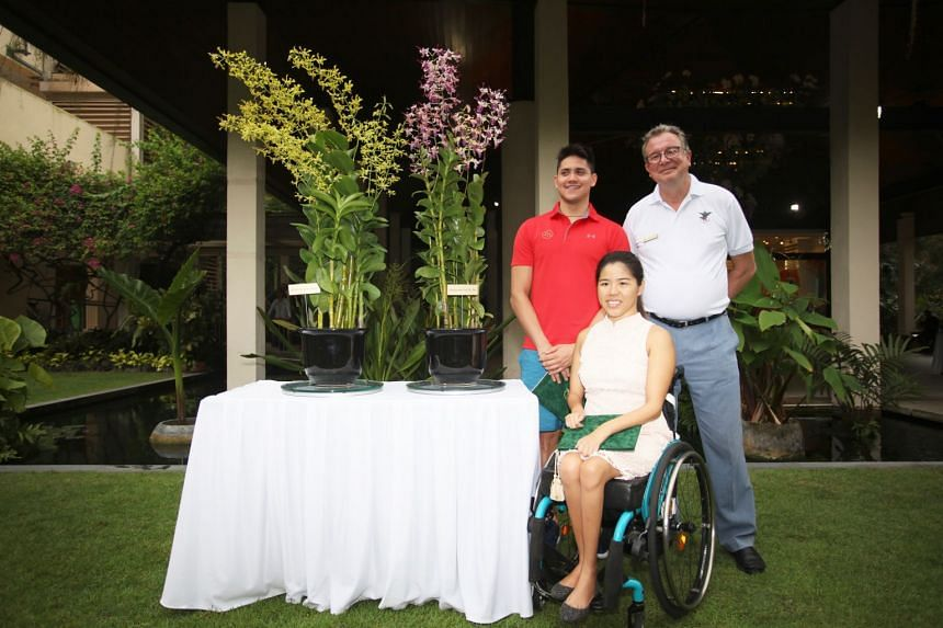 Swimmers Joseph Schooling and Yip Pin Xiu pose for a photo with Dr Nigel Taylor, group director of Singapore Botanic Gardens, and the orchids named after them.