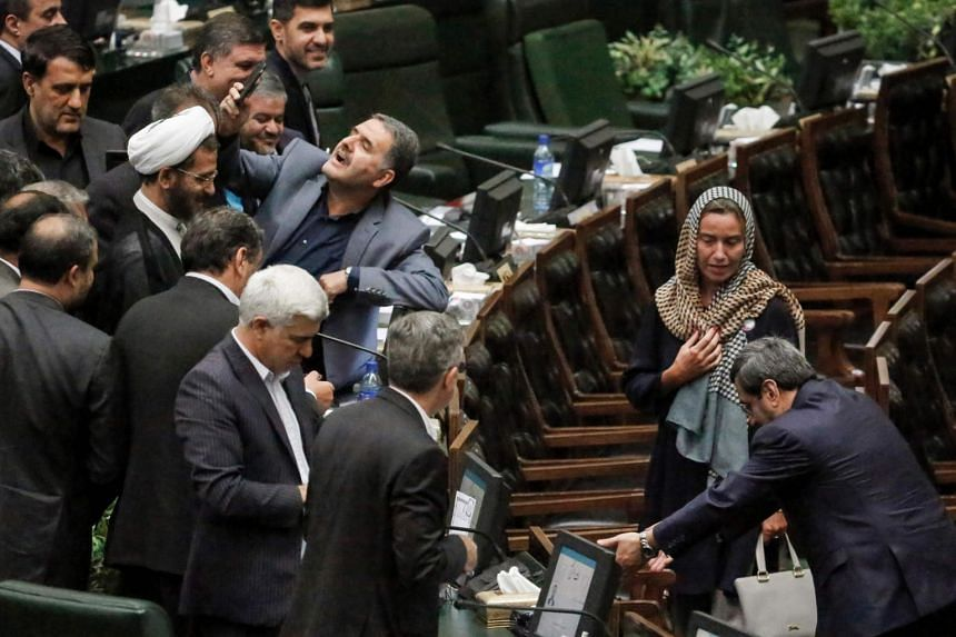 An Iranian MP (centre) takes a selfie as EU foreign policy chief Federica Mogherini walks by during the ceremony for the swearing in of Iran's President in Teheran, on Aug 5, 2017.