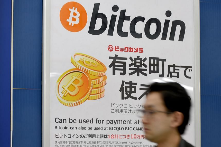 This April 7 photo shows a man walking past a signboard informing customers that Bitcoin can be used for payment at a store in Tokyo.