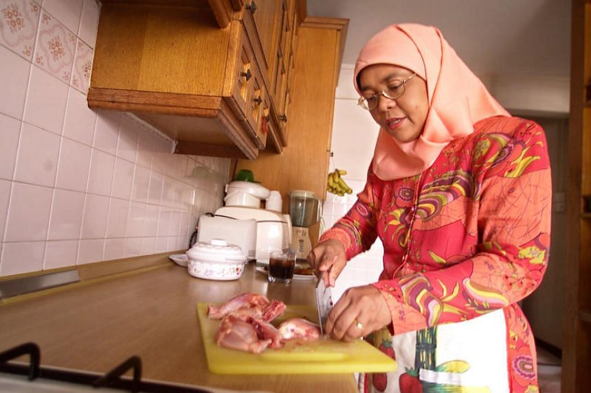 Madam Halimah Yacob seen here cooking in the kitchen of her HDB flat.