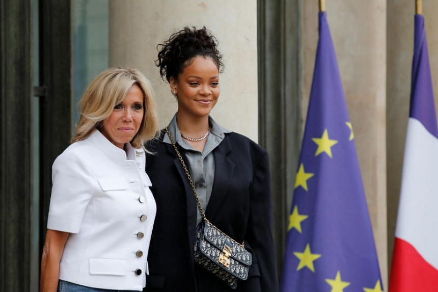 Brigitte Macron, wife of the French President, welcomes pop star Rihanna to the Elysee Palace in Paris on July 26, 2017.