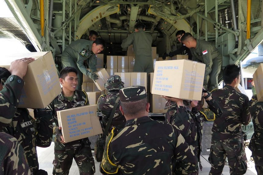 SAF personnel and Philippine army soldiers unloading aid supplies at Laguindingan International Airport on Aug 7, 2017.