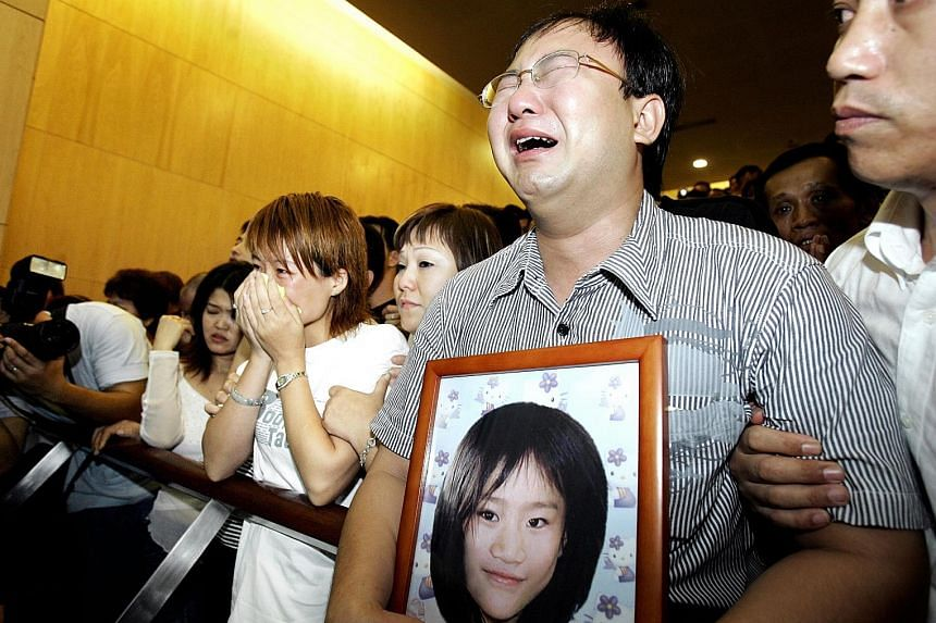 The parents of Huang Na, eight, who was killed in 2004, at the cremation at Mandai Crematorium. The story of her murder is one of the 25 that are published in Guilty As Charged.
