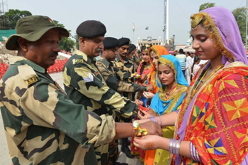 Indian schoolgirls tying sacred thread, or rakhi, onto the wrists of soldiers from the Indian Border Security Force during a ceremony observing the festival of Raksha Bandhan at the India-Pakistan Wagah border post about 35km from Amritsar, in the no