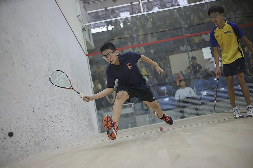 Benjamin Koh of ACS (I) playing against Fairfield Methodist's Daven Wong (in yellow) in the opening match of the Schools National C Division final. Daven won the match 8-11, 6-11, 11-2, 11-6, 11-7.