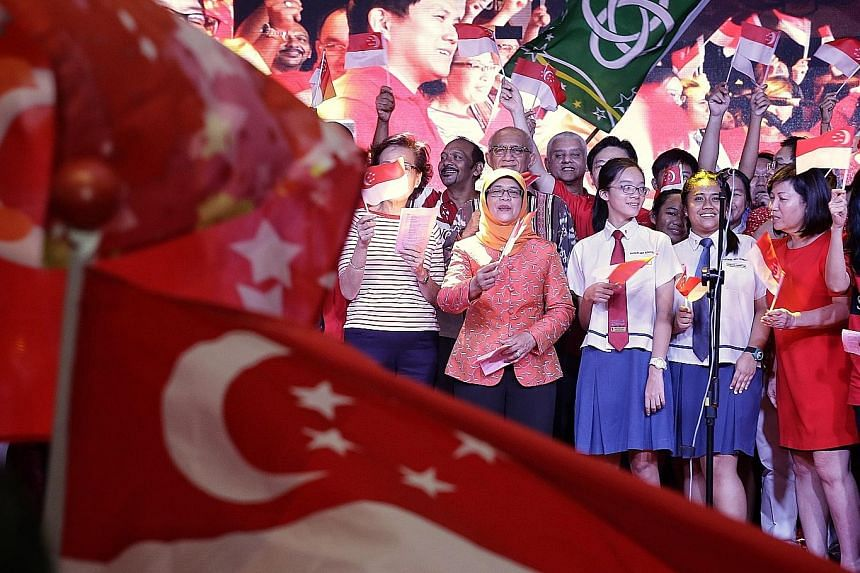 Madam Halimah Yacob, with her husband Mohammed Abdullah Alhabshee behind her, joining in a mass singing of National Day songs at the Marsiling National Day dinner celebration on Sunday.