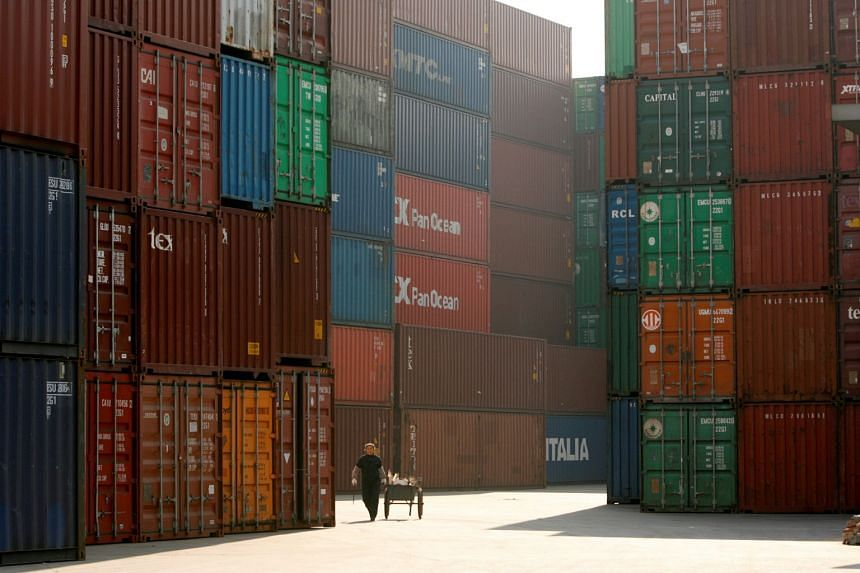A woman walks past containers at a port in Shanghai.
