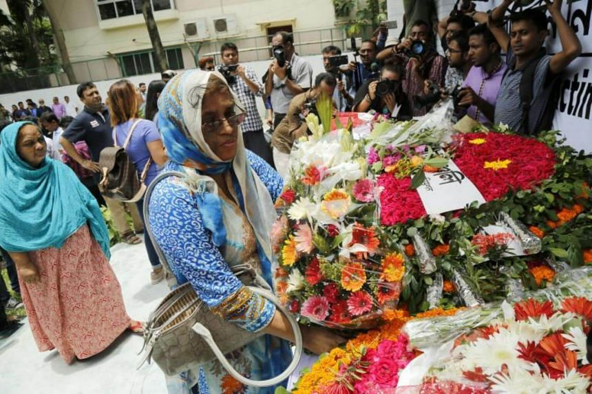 People pay their respects with flowers in front of the newly constructed building where the Holey Artisan Cafe used to be in Gulshan in Dhaka, Bangladesh on July 1, 2017.